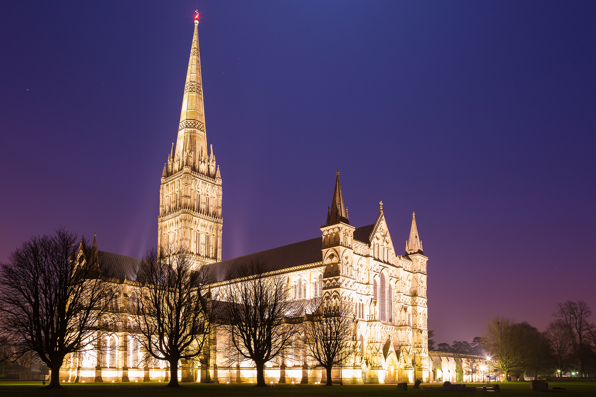 Photo of Salisbury cathedral on a moonlit evening, Wiltshire, England. Shot as the moon shone over the spire just after dusk.