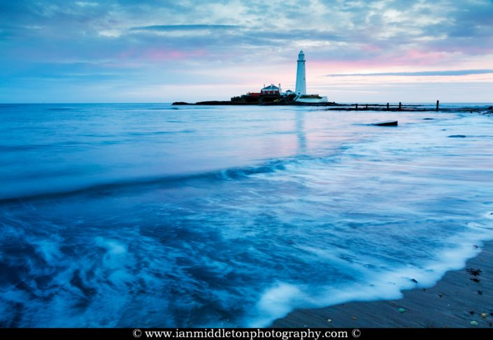 Saint Mary's Lighthouse on Saint Mary's Island, situated north of Whitley Bay, Tyne and Wear, North East England. Seen at dawn from the beach beside the causeway that runs out to the island. Whitley Bay is situated just north of Newcastle.