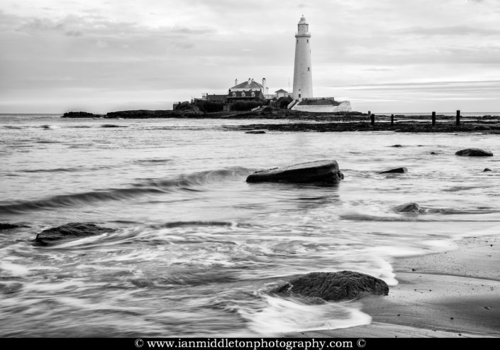 Black and white photo of Saint Mary's Lighthouse on Saint Mary's Island, situated north of Whitley Bay, Tyne and Wear, North East England. Seen at sunrise from the beach beside the causeway that runs out to the island. Whitley Bay is situated just north of Newcastle.