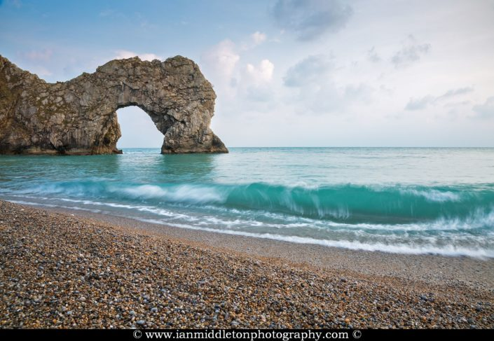 The late afternoon sun casts a warm glow over Durdle Door rock arch and beach, Dorset, England. Durdle door is one of the many stunning locations to visit on the Jurassic coast in southern England.