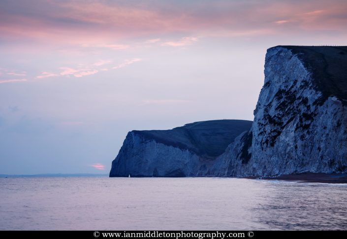 View across the cliffs to Bats Head from Durdle Door beach as the sun goes down for the evening, Dorset, England. Durdle door is one of the many stunning locations to visit on the Jurassic coast in southern England.