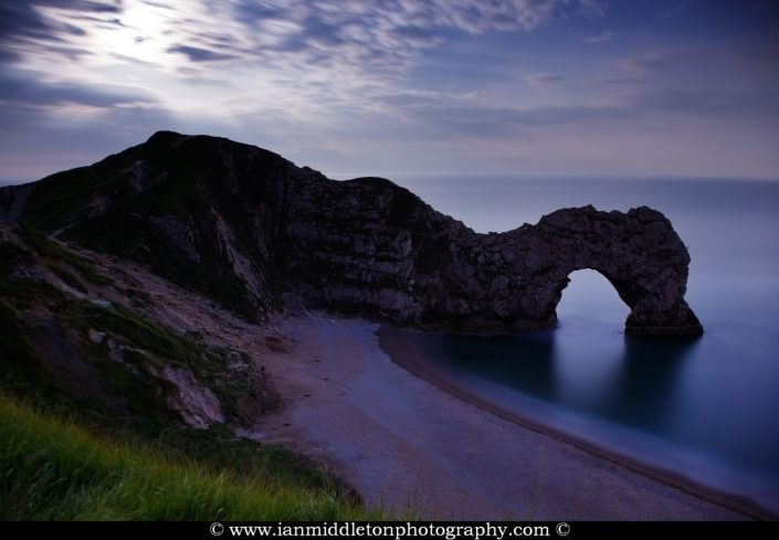 Durdle Door in the evening with the rising moon above it, Dorset, England. Durdle door is one of the many stunning locations to visit on the Jurassic coast in southern England.