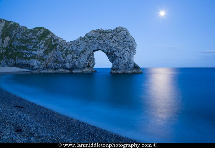 Close up of Durdle Door in the evening with the rising moon above it, Dorset, England. Durdle door is one of the many stunning locations to visit on the Jurassic coast in southern England.