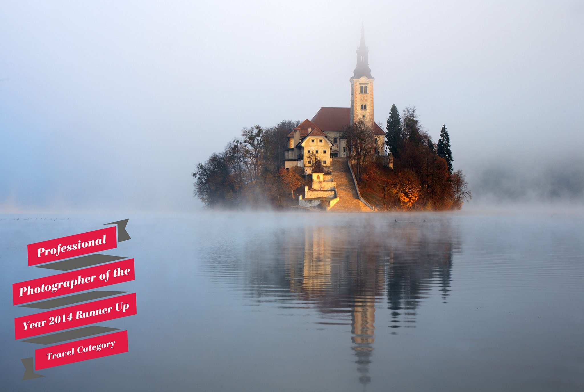 The famous Island church emerging as the morning sun breaks through an icy mist over Lake Bled. 3rd place in the Professional Photographer of year 2014 competition.