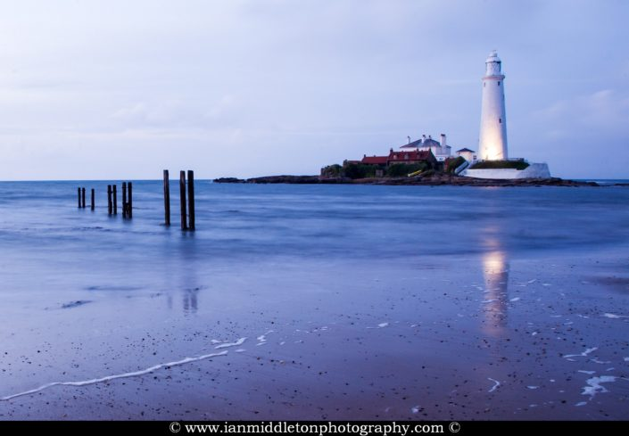 Saint Mary's Lighthouse on Saint Mary's Island, situated north of Whitley Bay, Tyne and Wear, North East England. Seen at dusk from the beach beside the causeway that runs out to the island. Whitley Bay is situated just north of Newcastle.