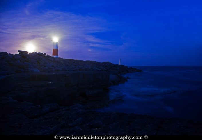 Lighthouse at Portland Bill at dusk with the moon rising over the rock beside it, near Weymouth, Jurassic Coast, Dorset, England.