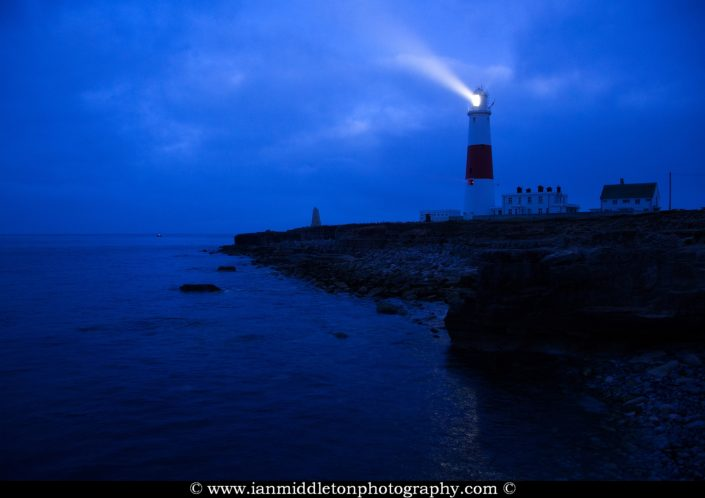 Lighthouse at Portland Bill shining at dawn, near Weymouth, Jurassic Coast, Dorset, England.
