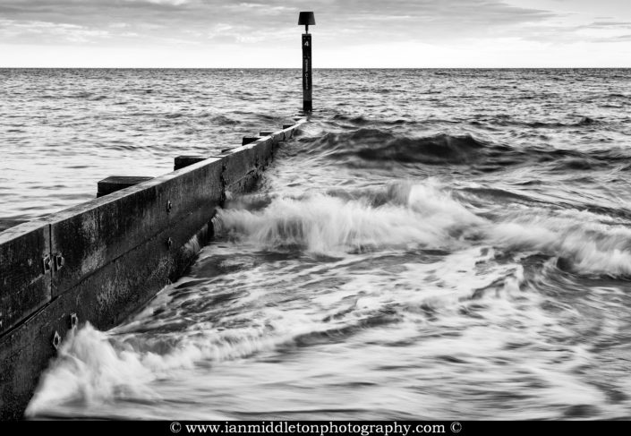 Waves crashing against Bournemouth Beach groyne in black and white, Dorset, England