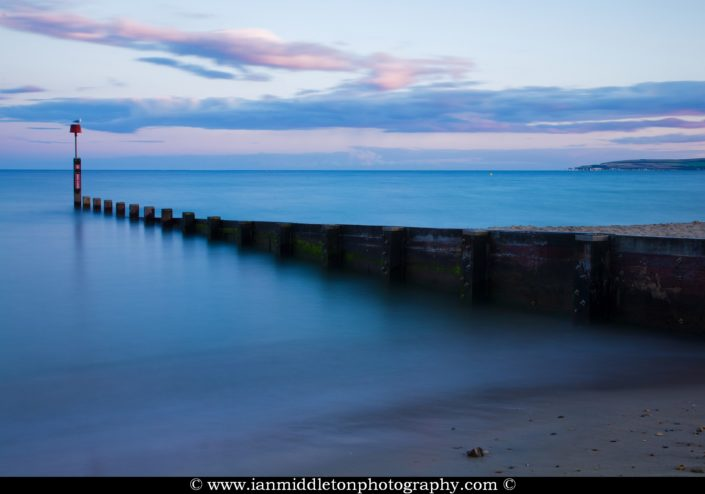 Bournemouth groyne, beach and seafront at sunset. old Harry cliffs can also be seen on the far right.