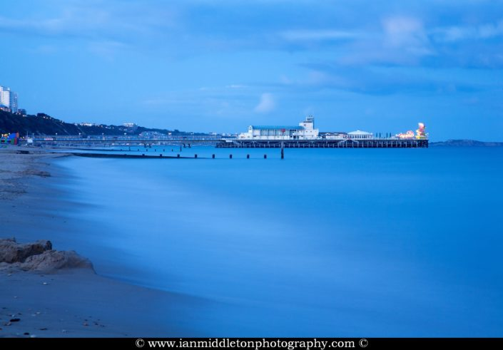 Bournemouth Pier and seafront at dusk. Highcliffe can also be seen on the far right.