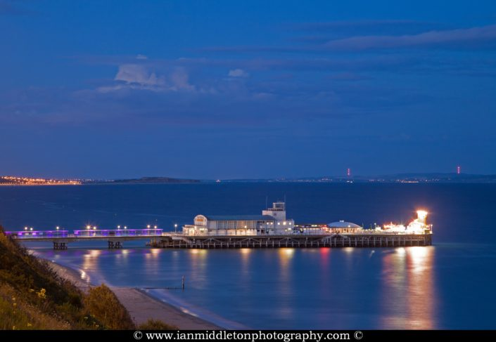 Bournemouth Pier and seafront at dusk. Highcliffe can also be seen on in the distance.