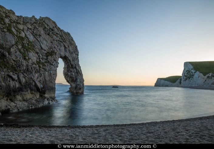 Durdle Door beach after the sun has disappeared over the cliffs, Dorset, England. Durdle door is one of the many stunning locations to visit on the Jurassic coast in southern England.