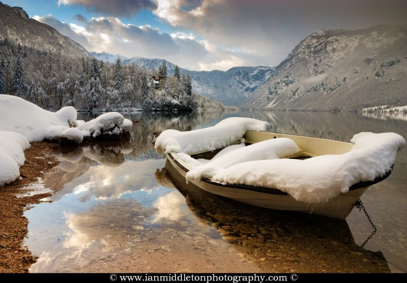 Snow covered boat on Lake Bohinj in Winter, Slovenia.