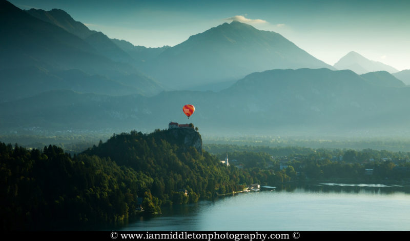 View across Lake Bled to a hot air balloon flying over the clifftop castle from Ojstrica, Slovenia.