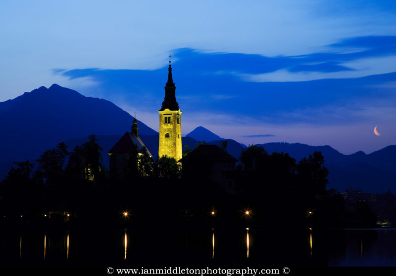 View across the beautiful Lake Bled, island church of the assumption of Mary, all topped off with the crescent of the waning moon at dawn, Slovenia.