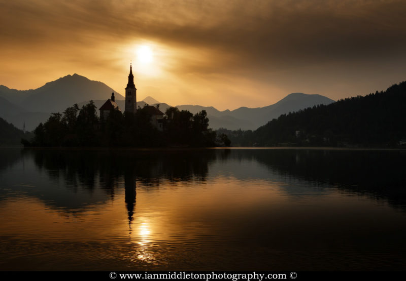 Sun rising over Lake Bled and the island church of the assumption of Mary with the Karavanke mountains in the background, Slovenia. To the left of the church is Mount Stol, the highest peak in the Karavanke mountain range.