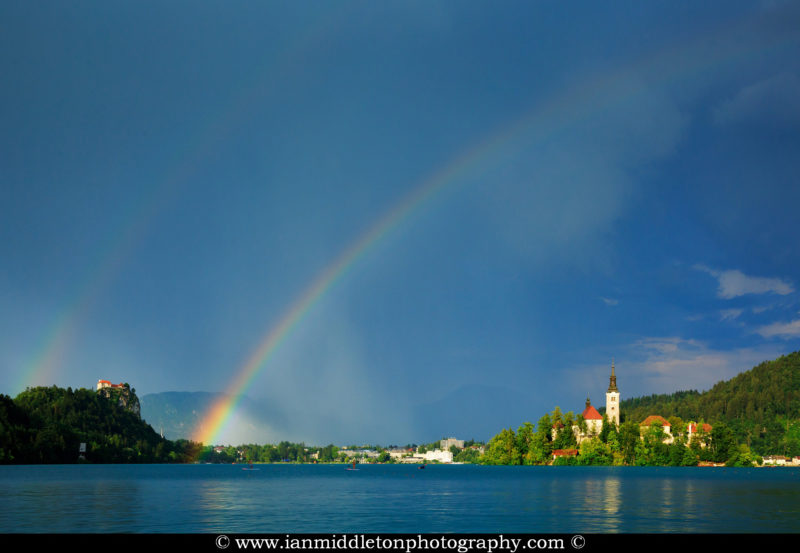 Beautiful light across to the beautiful Lake Bleds island church and hilltop castle as a storm blows over and produces a double rainbow right over the church and surrounding hills, Slovenia.