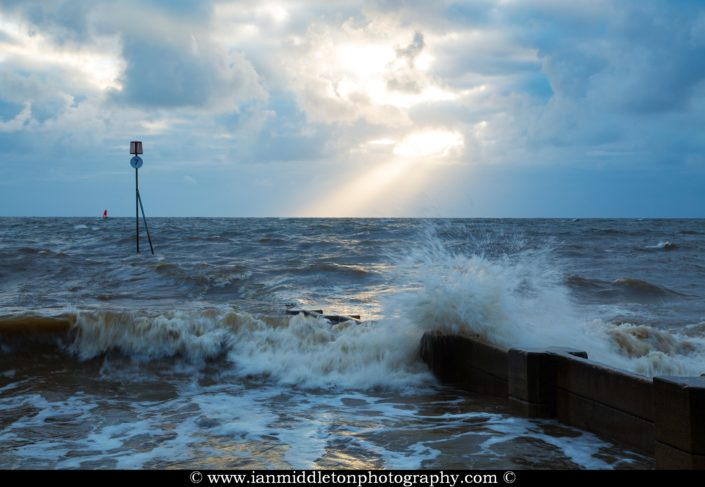 Waves crashing over groyne at Hunstanton beach at sundown, West Norfolk, England.