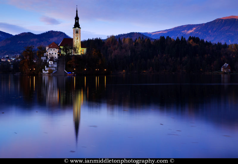 View across the beautiful Lake Bled, island church at dusk with the Karavanke mountains in the background, Slovenia. Lake Bled is Slovenia's most popular tourist destination and the Karawanke mountains form the border between Slovenia and Austria.