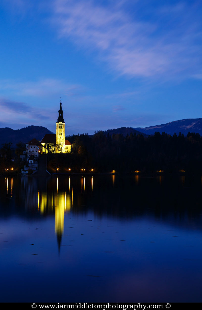 View across the beautiful Lake Bled and island church at dusk, Slovenia. Lake Bled is Slovenia's most popular tourist destination and the Karawanke mountains form the border between Slovenia and Austria.