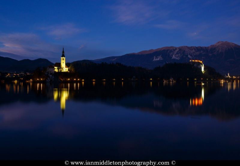 View across Lake Bled at night to the island church of the asssumption of Mary and the hilltop castle, Slovenia.