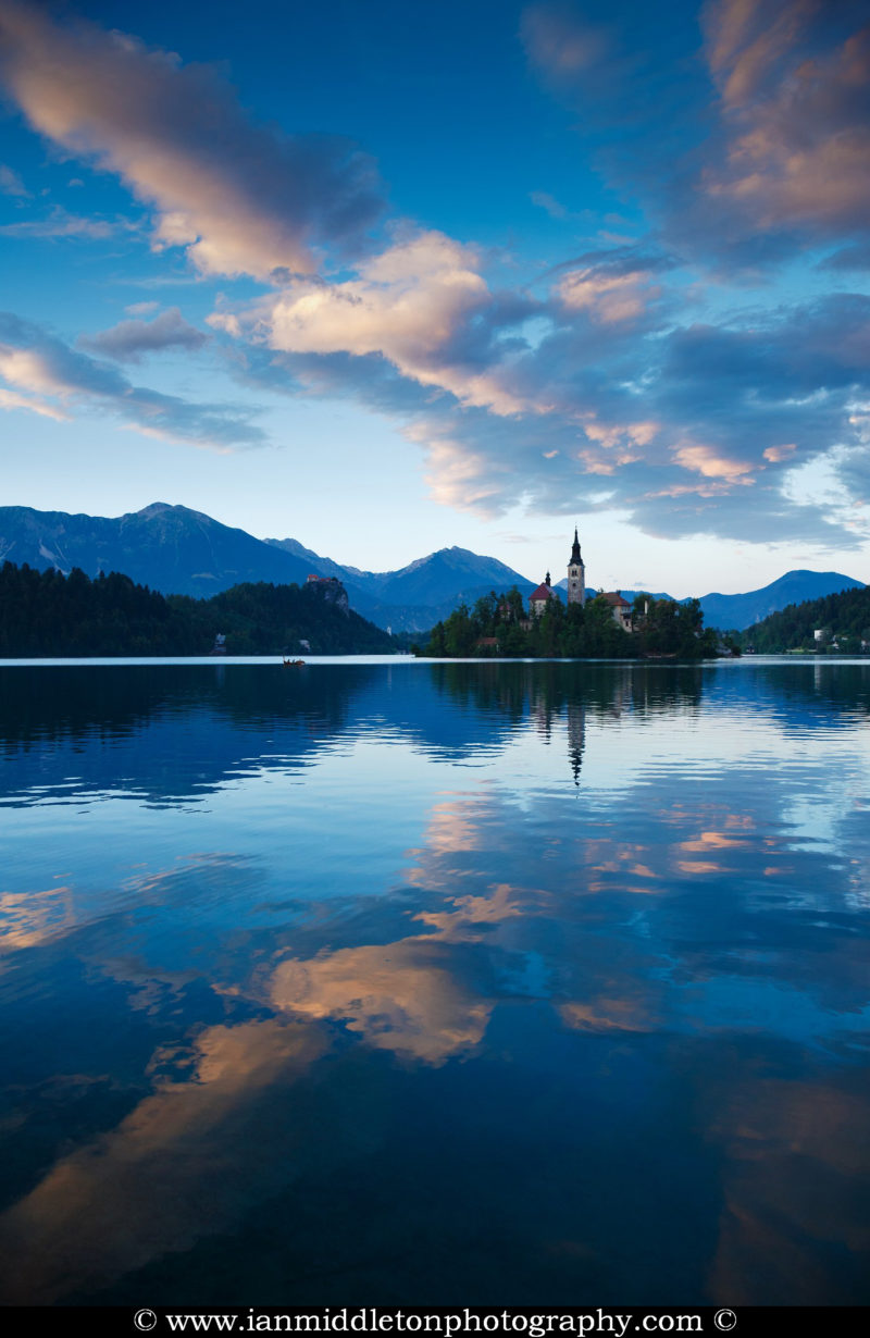 View across the beautiful Lake Bled, island church and hilltop castle at sunset with the beautiful Karawanke mountains in the background, Slovenia. Lake Bled is Slovenia's most popular tourist destination and the Karawanke mountains form the border between Slovenia and Austria.