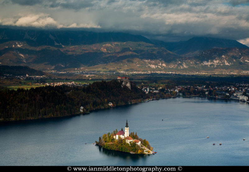 View across Lake Bled to the island church and clifftop castle from Mala Osojnica in autumn, Slovenia.