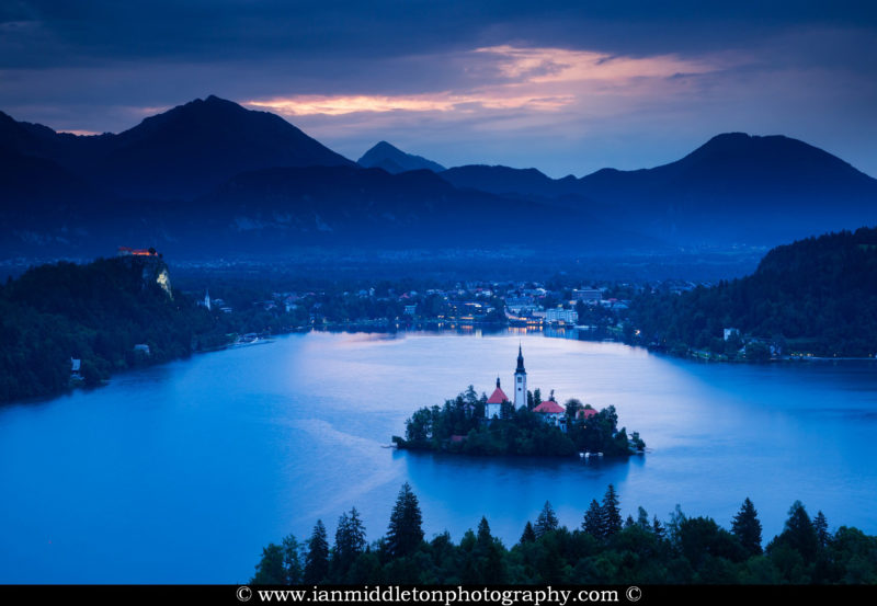 View across Lake Bled to the island church and clifftop castle from Ojstrica, Slovenia.
