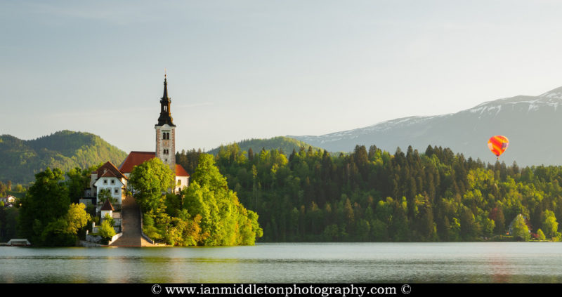 A hot air balloon rising beside the mountains behind Lake Bled's island church, Slovenia.