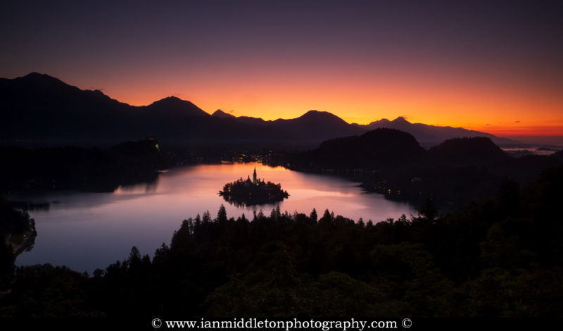 Sunrise view across Lake Bled to the island church and clifftop castle from Ojstrica, Slovenia. Here you can see the Karavank Alps and the Kamnik Alps