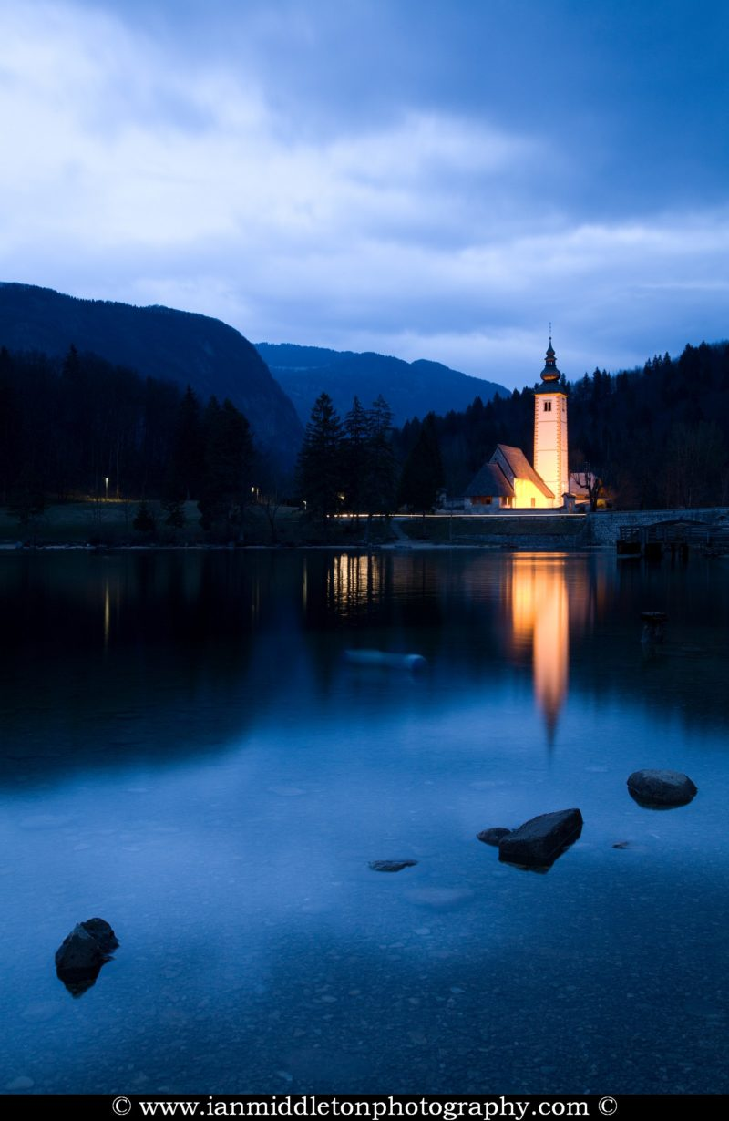 The Church of Saint John (Janez) lit up at dusk and reflected in the beautiful Lake Bohinj at dusk, Triglav National Park, Slovenia. This is the largest natural permanent lake in Slovenia situated in a glacial hollow of a dead end valley. The lake has many moods and no matter what the time of year, never fails to produce stunning scenes from all angles.