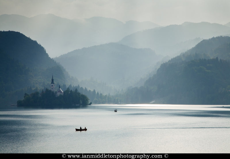 Sunlight breaks through the mist over Lake Bled, Slovenia