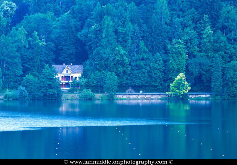 View across Lake Bled to an old villa by the roadside, Gorenjska, Slovenia