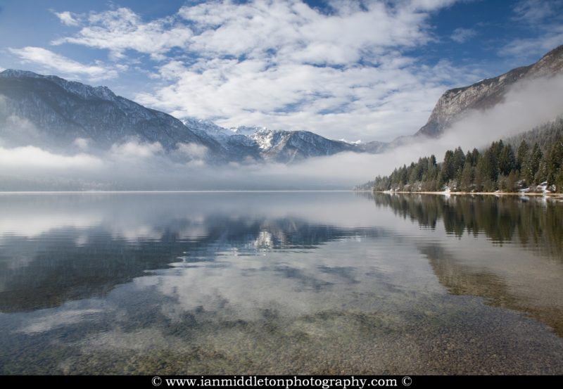 View across Lake Bohinj as the sun burns away the morning mist on New Years Day 2012, Triglav National Park , Slovenia