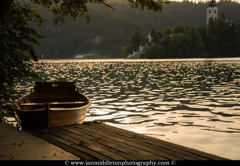 Rowing boat tied up on Lake Bled at sunset, Slovenia .
