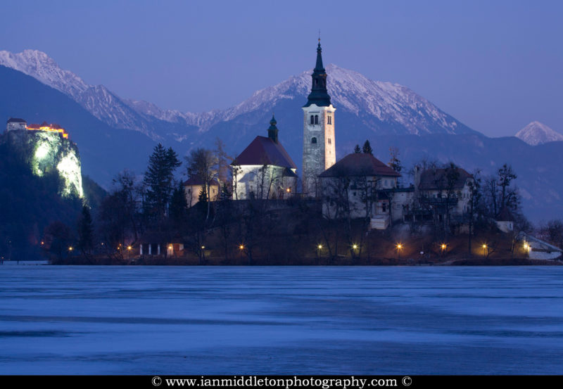 View across the beautiful Lake Bled, island church and hilltop castle when the lake was frozen over. When the winter is cold enough, the lake freezes and people walk out to the island church.