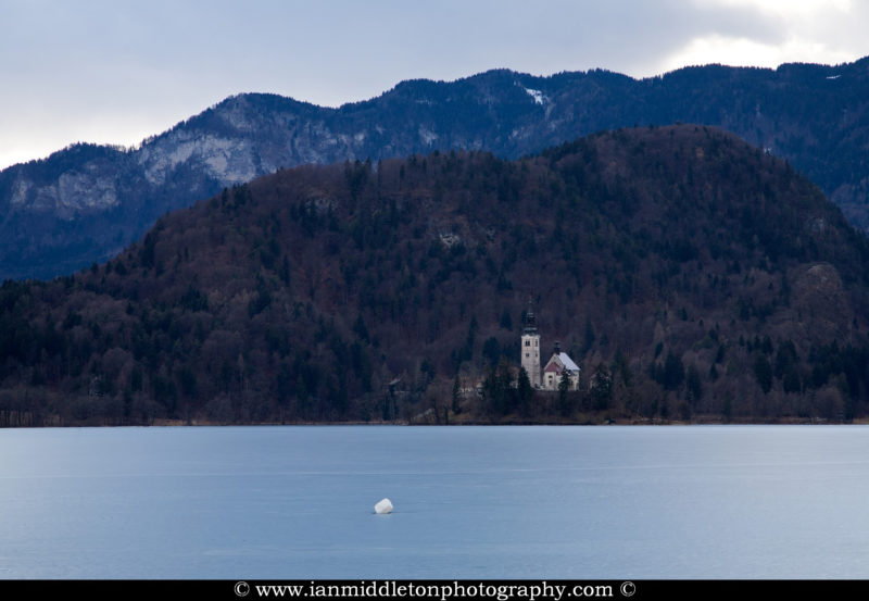 View across frozen Lake Bled to the island Pilgrimage Church of the Assumption of Mary, Slovenia .