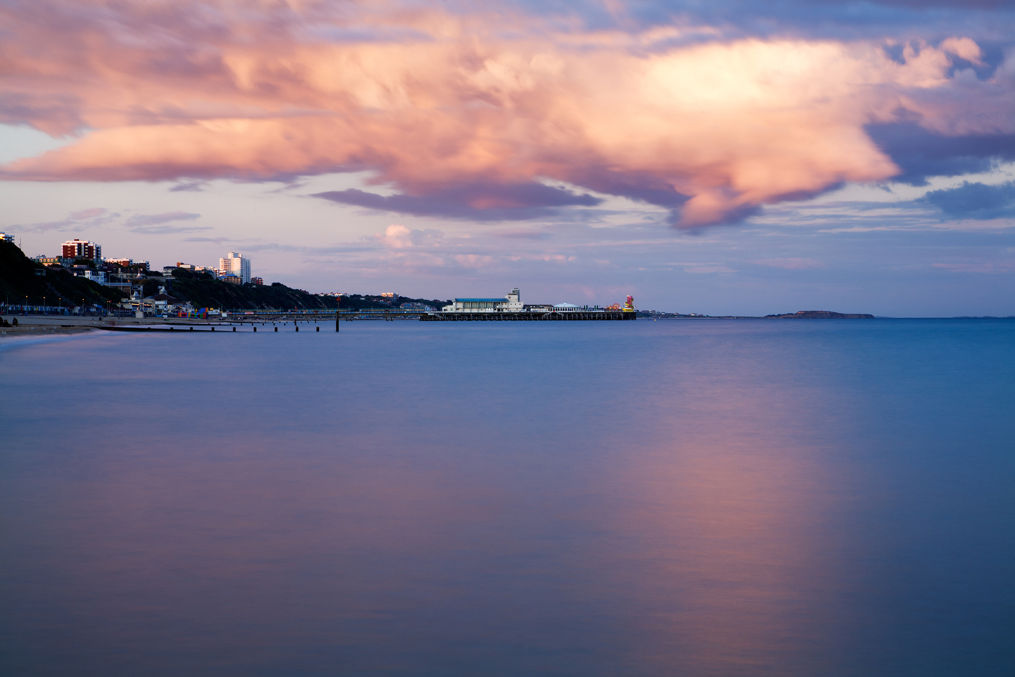 Bournemouth Pier and seafront as a storm cloud drifts over as is illuminated pink by the sunset. Highcliffe can also be seen on the far right.