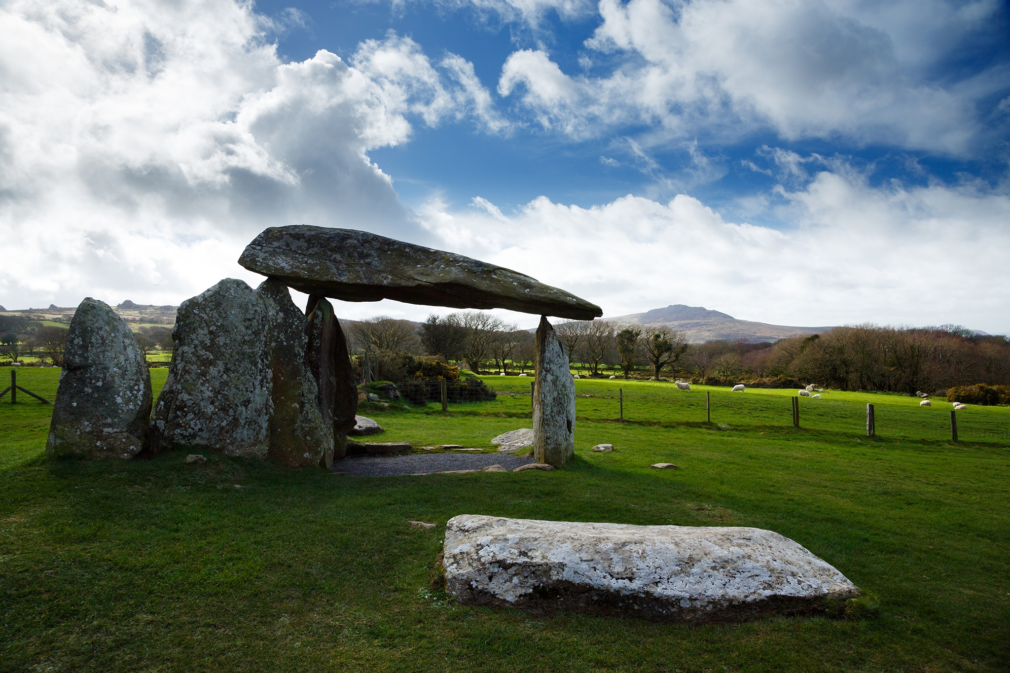 Pentre Ifan Neolithic Burial Chamber, Pembrokeshire, Wales. The Dolmen's huge capstone is delicately balanced on three uprights. Once known as Arthurs' Quoit, Pentre Ifan means Ivan's Village. This monument, dating back to about 3500 BC and unusually oriented north-south, stands on the slopes of a ridge commanding extensive views over the Nevern Valley. The capstone weighs over 16 tons; it is 5m (16ft 6in) long and 2.4m (8ft) off the ground.