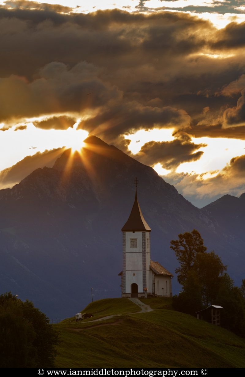 Jamnik church of Saints Primus and Felician at dawn, perched on a hill on the Jelovica Plateau with the kamnik alps and storzic mountain in the background, Slovenia.