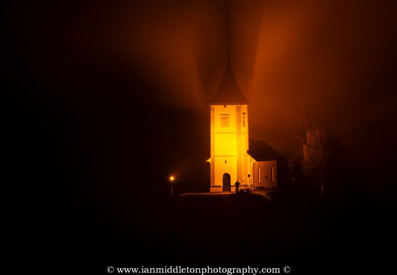 Jamnik church of Saints Primus and Felician in the mist at pre dawn, perched on a hill on the Jelovica Plateau, Slovenia.