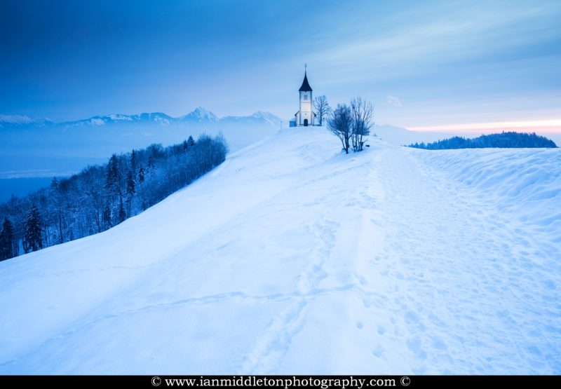 Jamnik church of Saints Primus and Felician just before sunrise in winter, perched on a hill on the Jelovica Plateau, Slovenia.