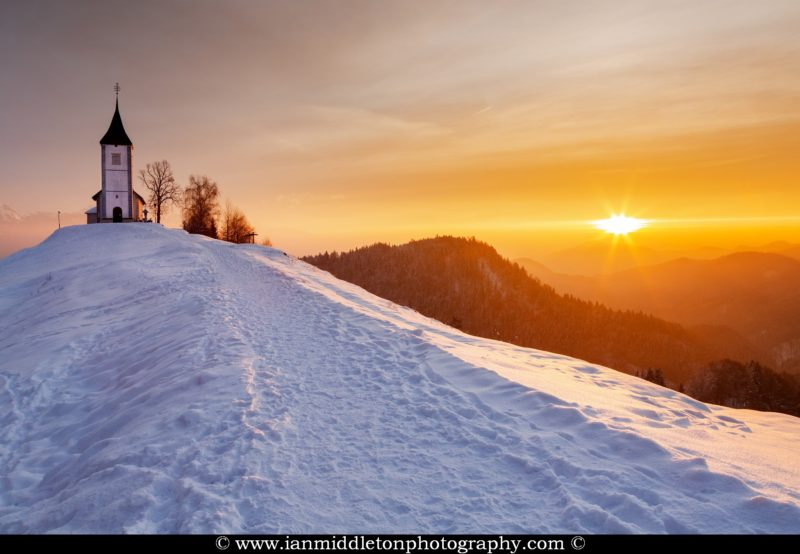 Jamnik church of Saints Primus and Felician at sunrise in winter, perched on a hill on the Jelovica Plateau, Slovenia.