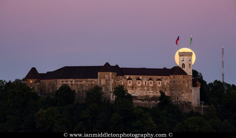 View across to the Ljubljana Castle as the full moon rises behind the tower at sunset. Seen from Tivoli Park, Ljubljana, Slovenia.