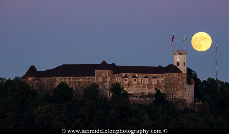 View across the to Ljubljana Castle as the full moon rises beside the tower at sunset. Seen from Tivoli Park, Ljubljana, Slovenia.
