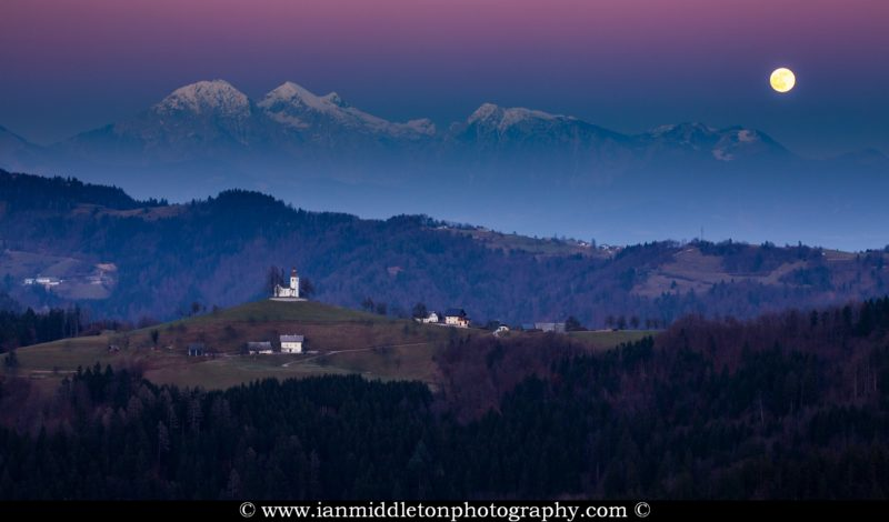 The full moon rising in winter over the mountains behind Sveti Tomaz nad Praprotnim (church of Saint Thomas) and the Kamnik Alps, Slovenia.