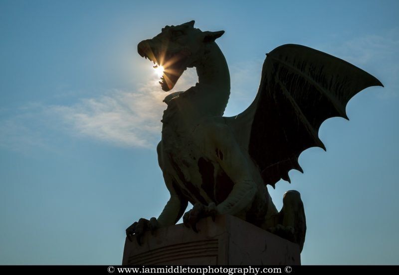 Sunburst through them mouth of a dragon on the Dragon Bridge in Ljubljana, Slovenia.