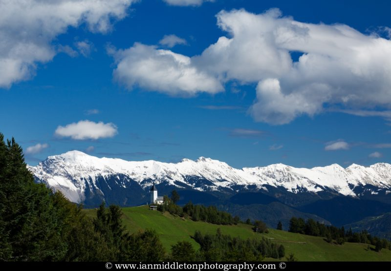 Jamnik church of Saints Primus and Felician, perched on a hill on the Jelovica Plateau with the snowcapped Karavanke Alps in the background, Slovenia. The alps have a fresh coating of snow on them after a 3 weeks of September rain.