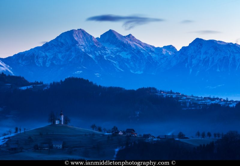View at dawn in winter from Rantovše hill across to Sveti Tomaz nad Praprotnim (church of Saint Thomas) and the Kamnik Alps, Slovenia.