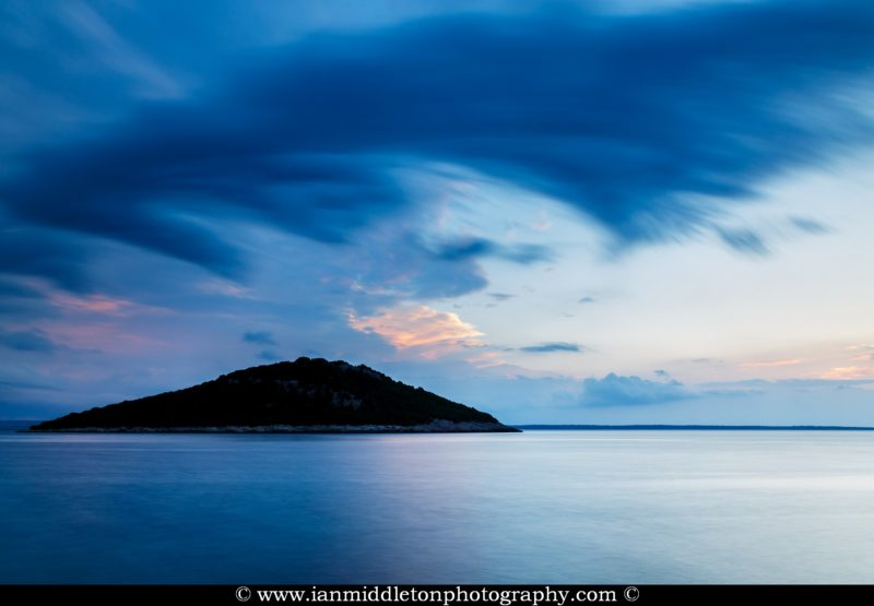 Storm moving in over Veli Osir Island at sunrise, seen from Zaosiri Beach, Cunski on Losinj Island, Croatia.